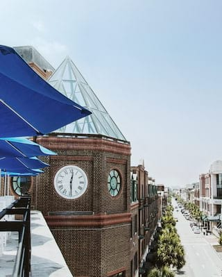 Rooftop bar beside a clocktower with views along a Charleston street