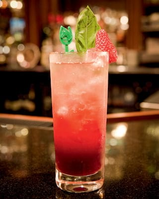 Close-up of a pink cocktail with mint and strawberry garnish