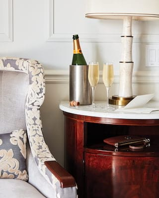 Chilled champagne with two full glasses on a marble-topped side table