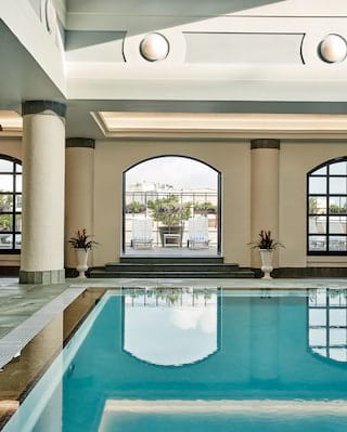 Hotel pool surrounded by arched windows with rooftop views