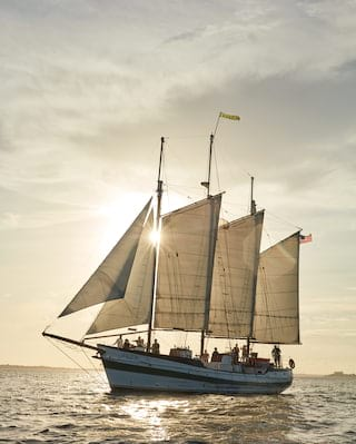 Traditional sailing boat gliding on waves at sunset