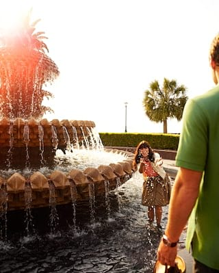 Lady splashing in large circular fountain at sunset