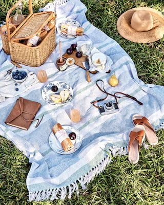 Picnic blanket and unpacked picnic basket laid out on grass