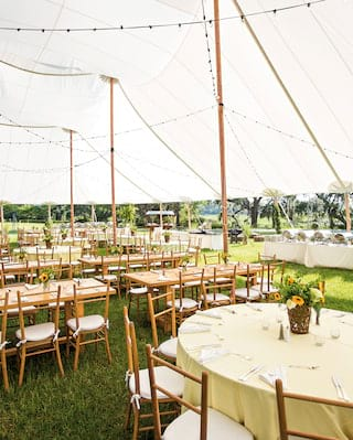 Bamboo chairs and tables set for a wedding on a lawn under a circus-style marquee