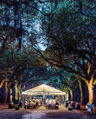 Glowing wedding tent at sunset with rows of large trees on either side