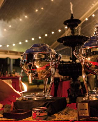 Close-up of aluminium coffee urns in a marquee lit by string lights