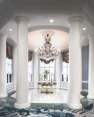 Light-filled circular room with white pillars and a crystal chandelier