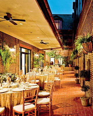 Circular banquet tables on a red-brick patio lined with potted plants