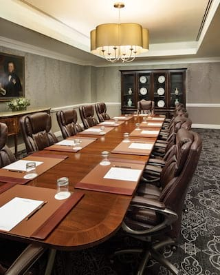 Polished mahogany boardroom table surrounded by black leather chairs