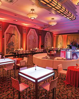 Square underlit tables surrounded by red chairs in a red backlit ballroom