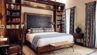 King-size bed surrounded by wooden bookcases in an elegant hotel room
