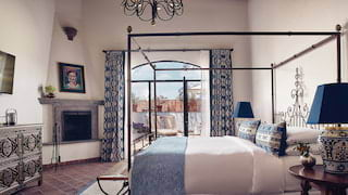 Elegant hotel room with ironwork four-poster bed and stone fireplace