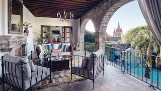 Luxurious hotel room terrace seating area with arched walls and stone floors