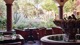Cloistered restaurant courtyard with tables for two and lush gardens beyond