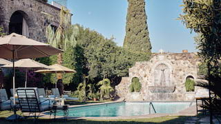 Outdoor hotel pool surrounded by a walled stone fountain and sunbeds