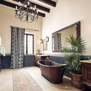 A stand-alone bath tub in a spacious bathroom with dark wood furnishings