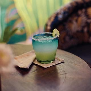 Close-up of a tequila cocktail in a blue glass garnished with lime