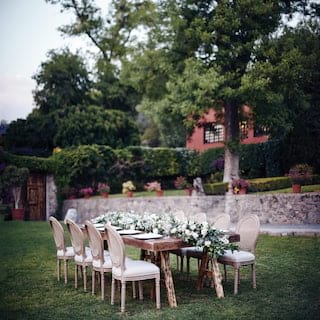 Outdoor banquet table in a garden with a full-length lily centrepiece