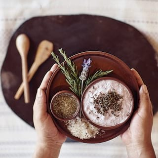 Two hands holding a bowl of spice and herb ingredients for a poultice