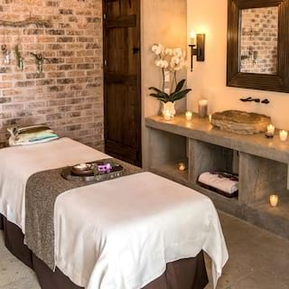 Spa treatment table with a stone side table lit with candles