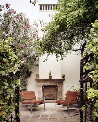Two lounge chairs in a garden courtyard either side of a stone fireplace