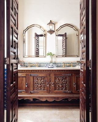 Two bathroom mirrors side-by-side above a carved wooden vanity cabinet