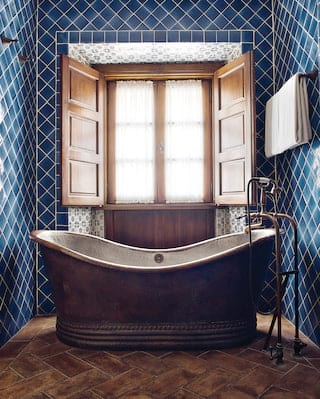 Close-up of a copper standalone bathtub surrounded by blue tiles