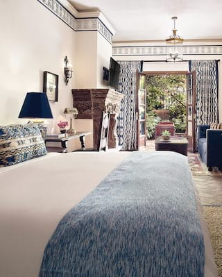 Bright hotel room with dark carved wood furniture and blue accents