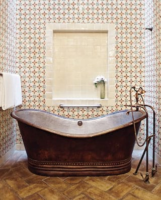 Close-up of a copper standalone bathtub surrounded by red and blue tiles