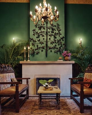 Green room with tan leather sofas either side of a large stone fireplace