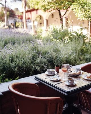 Table for two by a courtyard wall with flourishing lavender plants beyond