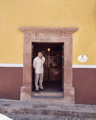 Smiling doorman peeking out from the stone doorway of a two-toned building