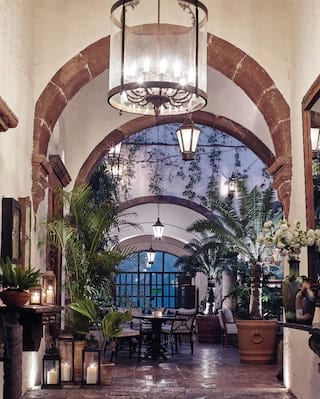 Leafy hotel courtyard in evening light with lantern lighting and potted palms