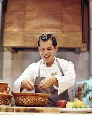 Smiling chef handling ingredients on a kitchen countertop in the Sazón
