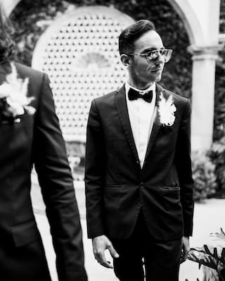 Two gentlemen in formal suits and bow ties walking in a garden