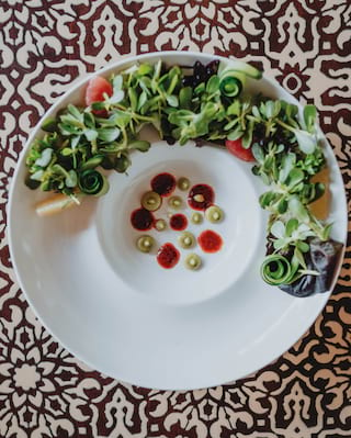Birds-eye-view of a vibrant soup and salad dish against a patterned backdrop