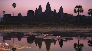 The silhouette of Angkor Wat in a pink sunset reflected in a lily pond