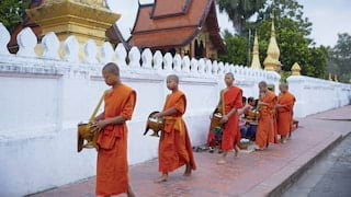 Five orange-robed monks in a Tak Bat procession outside a temple