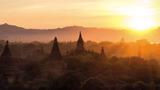 Silhouettes of temple spires among tree tops under an orange glowing sunset