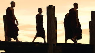 Silhouette of monks in robes walking along an ancient teak bridge at sunset