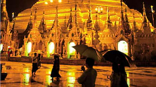 The silhouettes of visitors with umbrellas against the golden glow of Shwedagon Pagoda at night