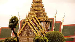 Ornate buddhist temple with gold-tipped arches leading to a golden pinnacle