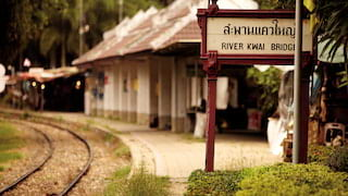 Colonial-style platform with a River Kwai Bridge station sign in Thai and English