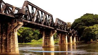 Motor boat sailing under Thailand's iconic Kwai River railway bridge