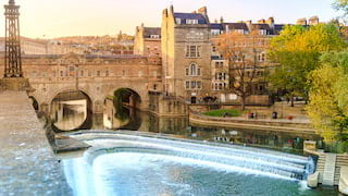View across a river of Bath city with a stone bridge and a row of Georgian houses