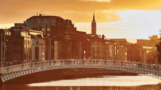 Penny Bridge in Dublin bowing over a river with the Dublin skyline behind