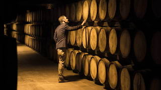 Man checking whisky barrels piled three-high in a low lit whisky cellar