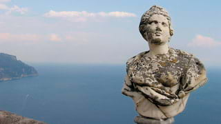 Ancient roman bust of a woman on a cliff top overlooking the Amalfi Coast at sunset
