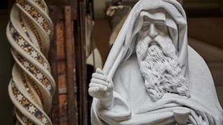 Close-up of a marble statue of Leonardo Da Vinci beside a spiral column