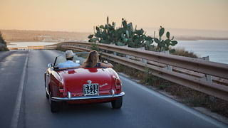 Gleaming, red, soft-top classic car on a seaside road at sunset